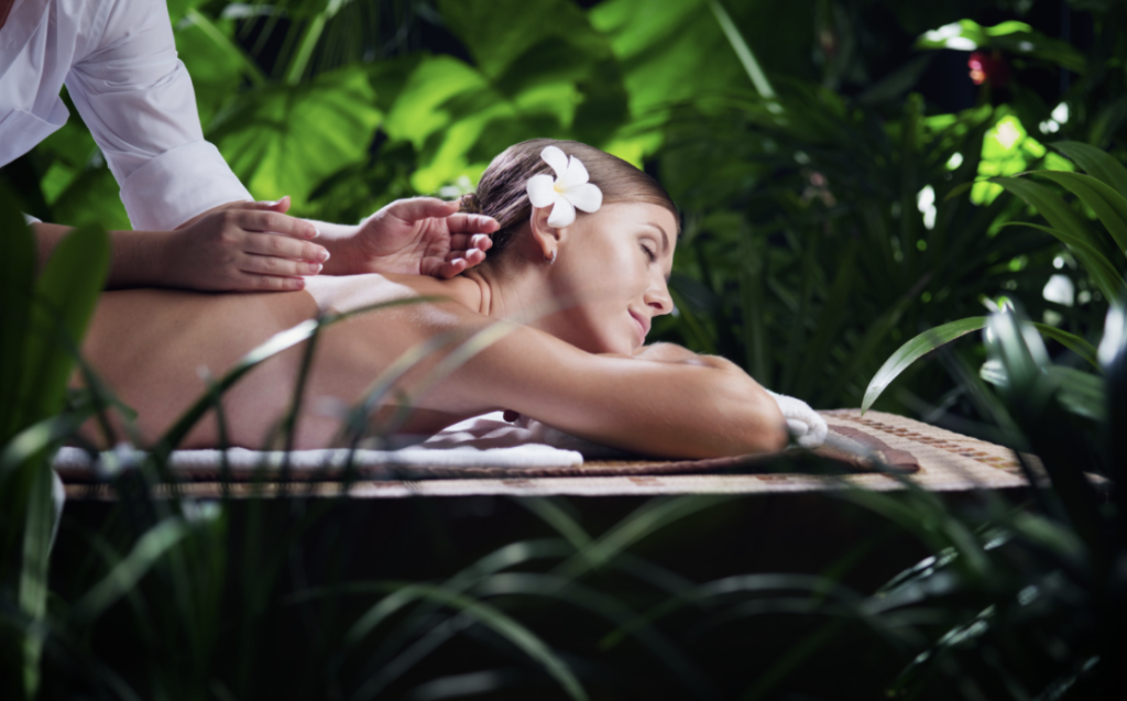Female getting massage surrounded by plants