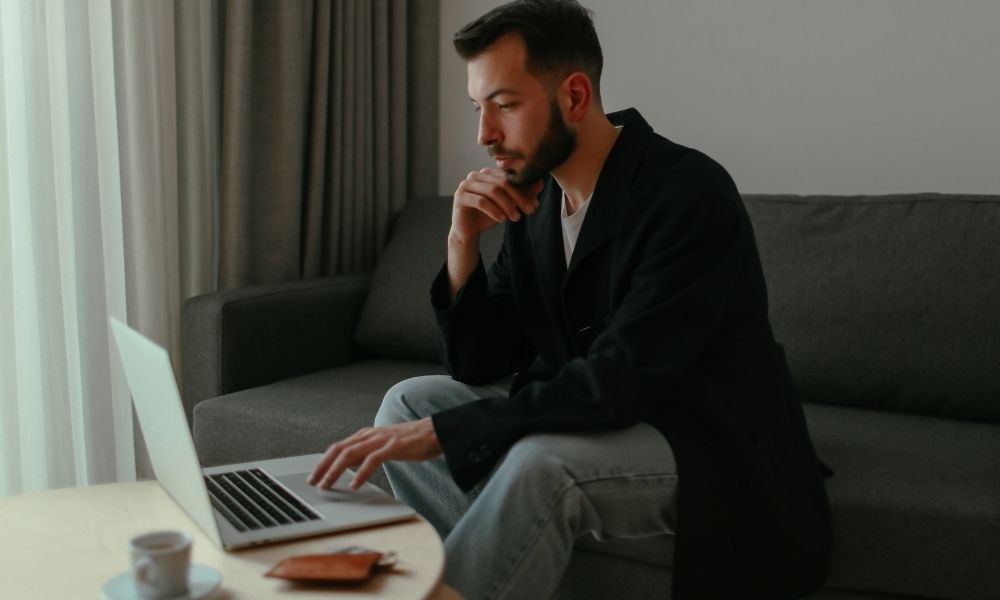 a man using a laptop to shop online and find a cbd store near him