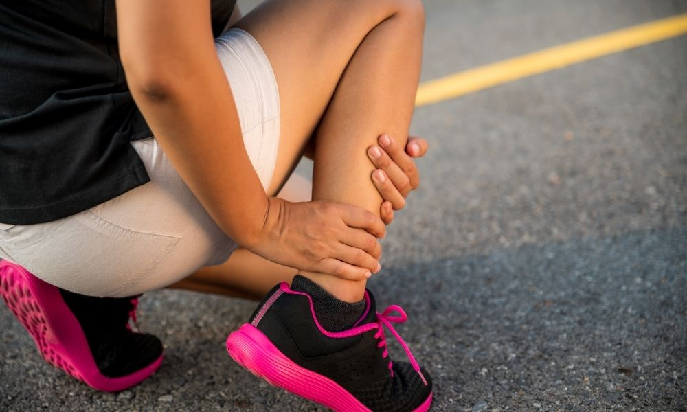 athletic woman bracing her right leg after running